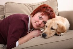 Pet and owner. A caucasian woman and her Labrador dog snuggling up on the sofa Royalty Free Stock Photos
