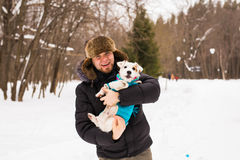 Pet owner, dog, and people concept - Young smiling caucasian man holding Jack Russell terrier outdoor in winter time. Royalty Free Stock Images