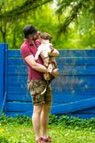 Young man enjoying a sunny day in the park with his dog. Pet owner receiving a kiss lick from his pet dog on the couch stock photo