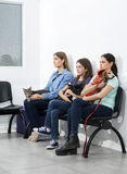 Pet Owners Sitting On Chairs In Waiting Area Royalty Free Stock Photos