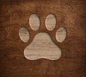 Pet paw print dog cat symbol engraved in wooden board