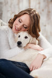 Pet's frienship. Young woman with her pet, golden retriever, relaxing together Stock Images