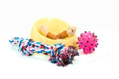 Pet supplies set about plastic bowl, rope, rubber toys with snack bone for dog or cat on white background. royalty free stock photo