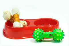 Pet supplies about snack bone in bowl with rubber toy isolated o. N white background royalty free stock photos