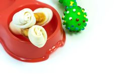 Pet supplies about snack bone in bowl with rubber toy isolated o. N white background royalty free stock photography