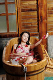 Petal bath. A young woman relaxing in a bath filled with flowers and petals Stock Photo