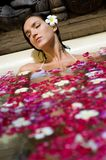 Petal Bath. A young woman relaxing in an outdoor bath filled with flowers and petals