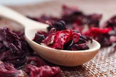 Petali di tè su un primo piano di legno del cucchiaio Macro foto dell'animale domestico rosso Immagini Stock
