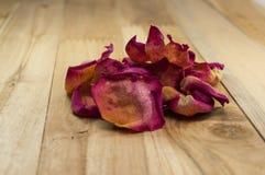 Petali rosa secchi su legno Fotografia Stock
