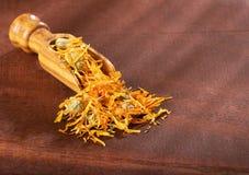 Petali secchi della calendula - calendula officinalis Fondo di legno fotografia stock