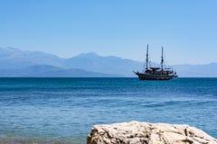 PETALIDI GREKLAND - AUGUSTI 13, 2017: Turister som tycker om havsresan på tappning, seglar skeppet i den Petalidi byn, Grekland Royaltyfri Bild