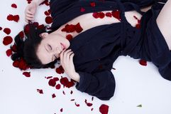 Petals. Relaxed girl lying down with rose petals Stock Photos