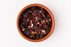 Petals of dry hibiscus tea in the clay pot isolated on white background. Top view royalty free stock photos