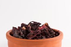 Petals of dry hibiscus tea in the clay pot isolated on white. Background stock photography