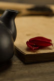 Petals of a flower on old blank open book on wooden background. Royalty Free Stock Images