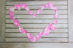 Petals of pink roses in a heart shape and a candle on a white wo Royalty Free Stock Photo
