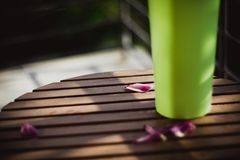 Petals of a pink tulip lies on a wooden table near green vase on sun stock photography