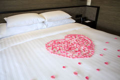 Petals of roses on a white honeymoon bed. In the room Stock Photo