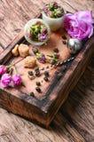 Petals of tea-rose for tea. Dry rose buds tea.Tea strainer and rosebuds on a wooden background Stock Images