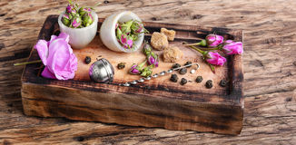 Petals of tea-rose for tea. Dry rose buds tea.Tea strainer and rosebuds on a wooden background Royalty Free Stock Images