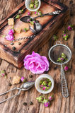 Petals of tea-rose for tea. Dry rose buds tea.Tea strainer and rosebuds on a wooden background Stock Photo