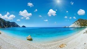 Petani Beach sunshiny panorama Kefalonia, Greece. Petani Beach Kefalonia, Greece. Summer sunshiny coast panorama with blue cloudy sky. Two shots stitch image Stock Photo
