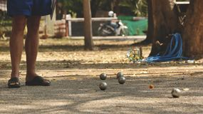 Petanque球和橙色木球在岩石围场有站立在树荫下的一个人的-晴天在公园 免版税图库摄影