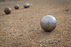 Petanque-Bälle auf einer sandigen Neigung mit anderem Metallball im BAC Stockfotografie