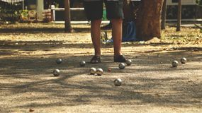 Petanque Balls and Orange Wooden Ball on Sandy Ground with a Man Standing in the Shade - Sunny Day in the Park. Petanque Balls and Orange Wooden Ball on Sandy Royalty Free Stock Image