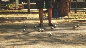Petanque bollar och orange träboll på Sandy Ground med ett mananseende i skuggan - Sunny Day i parkera Royaltyfri Bild
