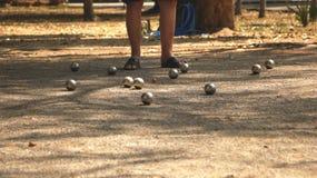 Petanque bollar och orange träboll på Sandy Yard med ett mananseende under trädet - Sunny Day i parkera Arkivfoto