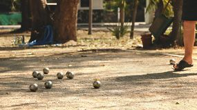Petanque klumpa ihop sig, och den orange träbollen på Sandy Yard med man` s lägger benen på ryggen Arkivbilder