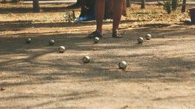 Petanque klumpa ihop sig, och den orange träbollen på Sandy Yard med man` s lägger benen på ryggen Arkivfoton