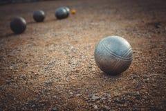 Petanque klumpa ihop sig på en sandig grad med annan metallboll Arkivfoto