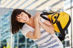 Petate que lleva del viajero feliz sobre hombro Imágenes de archivo libres de regalías