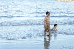 Petchaburi/Thailand - Mei 9 2018: Het jonge jongen spelen in het zand en golven op het strand stock foto's