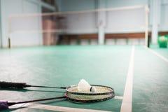 Peteca e raquete da bola do badminton no assoalho da corte Imagens de Stock Royalty Free