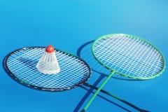 Peteca ou passarinho na raquete de badminton no fundo azul Conceito do esporte imagens de stock