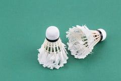 Peteca para fora usada worned dois do badminton na esteira verde da corte Fotos de Stock Royalty Free