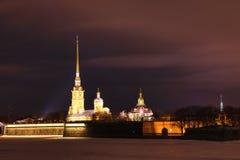 Peter e Paul Fortress de St Petersburg, Rússia na noite ou na noite e no rio de Neva cobertos com o gelo e a neve imagem de stock