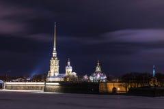 Peter e Paul Fortress de St Petersburg, Rússia na noite ou na noite e no rio de Neva cobertos com o gelo e a neve fotos de stock
