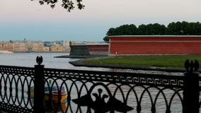 The Peter and Paul Fortress, fence embankment with the Russian coat of arms. Russia, Saint-Petersburg, 2 JULY 2016: pleasure river transport with tourists on stock video