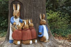 Peter Rabbit Scene. Mother and kids bunny rabbit sculptures made of wood beside a tree royalty free stock photography