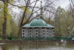 PETERHOF,俄罗斯- 2015年5月10日:有绿色屋顶的装饰亭子在池塘和喷泉附近 免版税图库摄影
