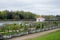 PETERHOF,俄罗斯- 2015年5月10日:降低Peterhof公园庭院,对池塘和一个偏僻的房子的一个看法 免版税库存图片