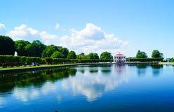 PETERHOF, HEILIGE PETERSBURG, RUSLAND - Juli 12, 2017: Mening van Eenzaam Huis met een vijver in zonnige dag, Park van Peterhof Stock Foto's