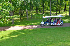 PETERHOF, RUSSIA. The excursion electric car with tourists goes on a path of Nizhny of park Royalty Free Stock Photo