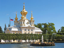 PETERHOF, RUSSIA. Fountains of square ponds against Church of Saints Peter and Paul Royalty Free Stock Images