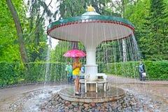 Peterhof, Russia La ragazza con un ombrello circa il cracker della fontana dell'ombrello nel parco di Nizhny Immagine Stock