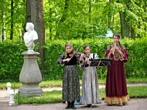 PETERHOF, RUSSIA. Three girls musicians give a concert in Nizhny park Royalty Free Stock Photos